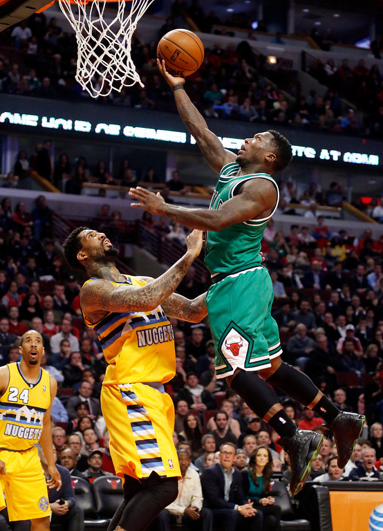 . Chicago Bulls guard Nate Robinson shoots over Denver Nuggets guard Wilson Chandler during overtime of an NBA basketball game, Monday, March 18, 2013, in Chicago. The Nuggets won 119-118. (AP Photo/Charles Rex Arbogast)