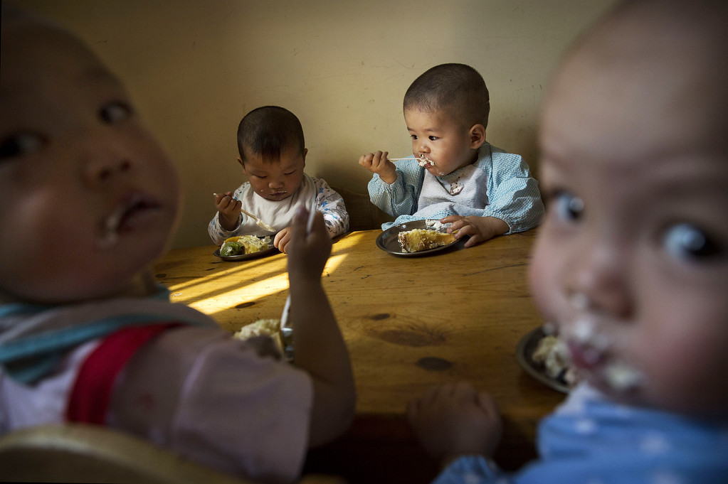. Young Chinese orphaned children eat during a feeding at a foster care center on April 2, 2014 in Beijing, China.  (Photo by Kevin Frayer/Getty Images)