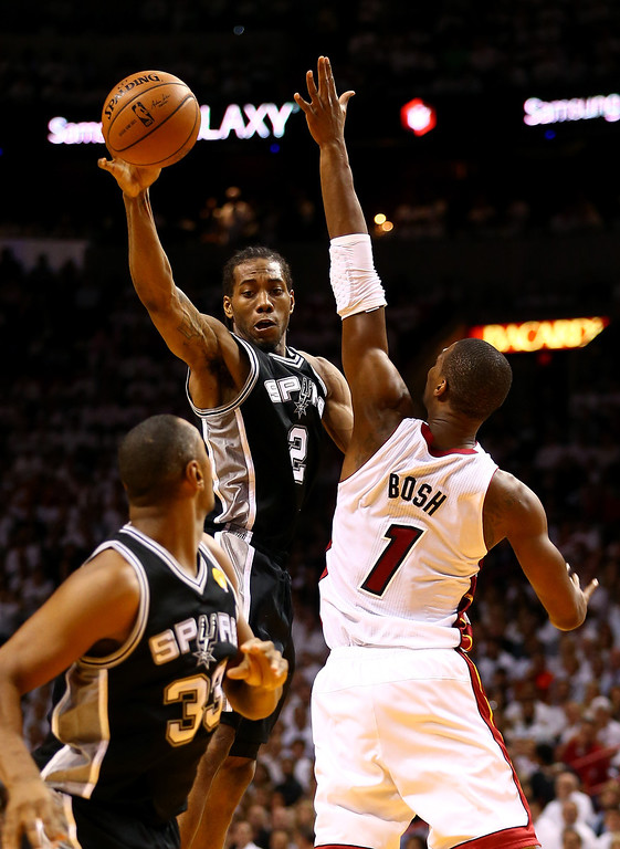 . MIAMI, FL - JUNE 10: Kawhi Leonard #2 passes to Boris Diaw #33 of the San Antonio Spurs as Chris Bosh #1 of the Miami Heat defends during Game Three of the 2014 NBA Finals at American Airlines Arena on June 10, 2014 in Miami, Florida.  (Photo by Andy Lyons/Getty Images)