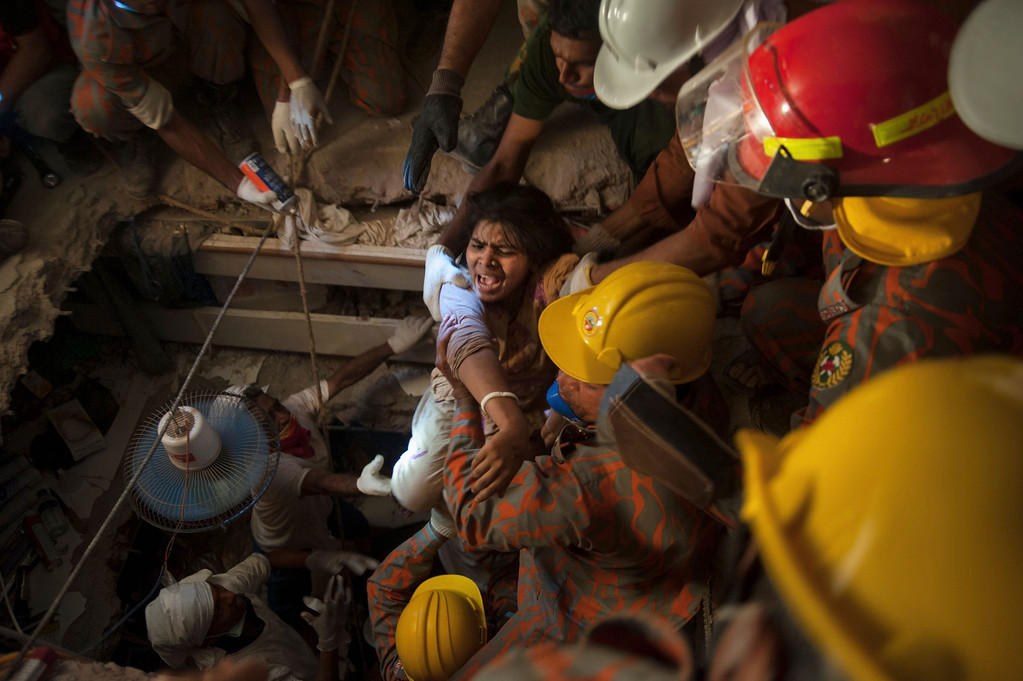 . Rescue workers rescue a garment worker from the rubble of the collapsed Rana Plaza building, in Savar, 30 km (19 miles) outside Dhaka April 27, 2013. Two factory bosses and two engineers were arrested in Bangladesh on Saturday, 72 hours after the collapse of a building where low-cost garments were made for Western brands, as the death toll rose to 340 but many were still being found alive. REUTERS/Stringer