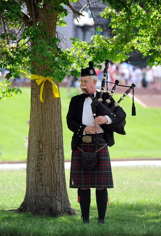 . Alex McIntosh finds shade under a tree as he practices his bagpipes for the Veterans Memorial Day Tribute in Lincoln State Park next to the parade route.(Photo By Kathryn Scott Osler/The Denver Post)