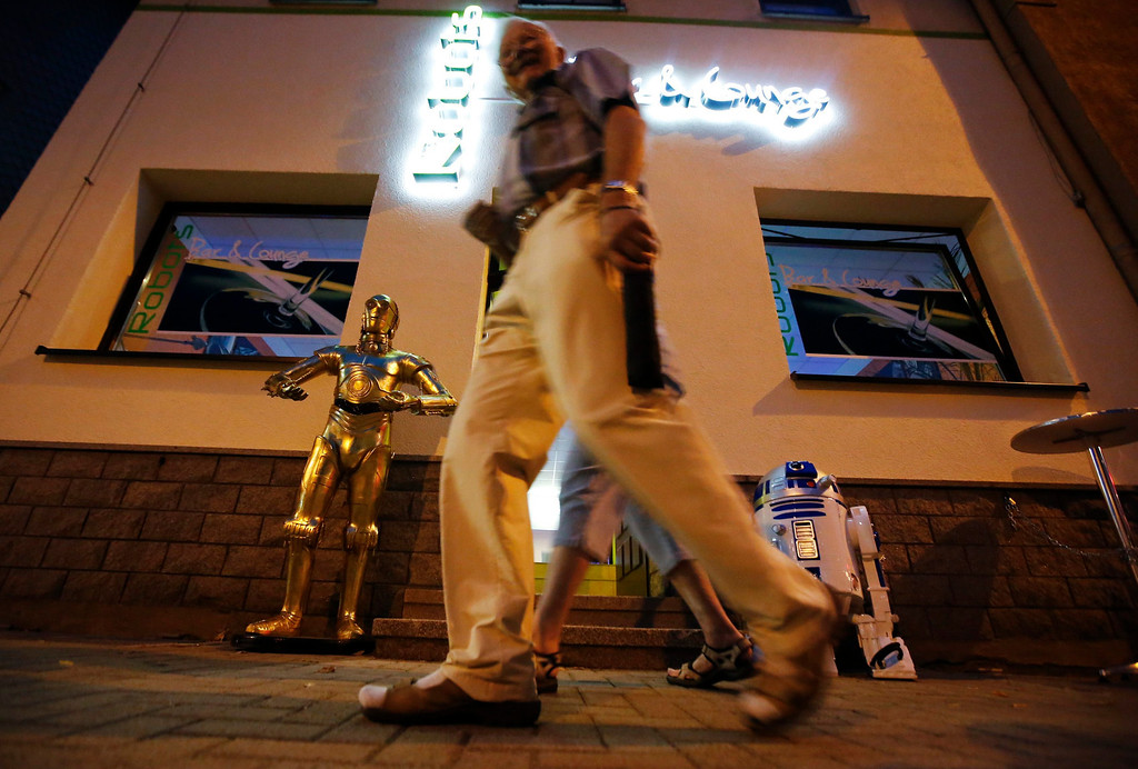 """. A pedestrian walks past the Robots Bar and Lounge where humanoid robot bartender \""""Carl\"""" is helping to serve customers, in the eastern German town of Ilmenau, July 26, 2013. \""""Carl\"""", developed and built by mechatronics engineer Ben Schaefer who runs a company for humanoid robots, prepares spirits for the mixing of cocktails and is able to interact with customers in small conversations. Picture taken July 26, 2013. REUTERS/Fabrizio Bensch"""