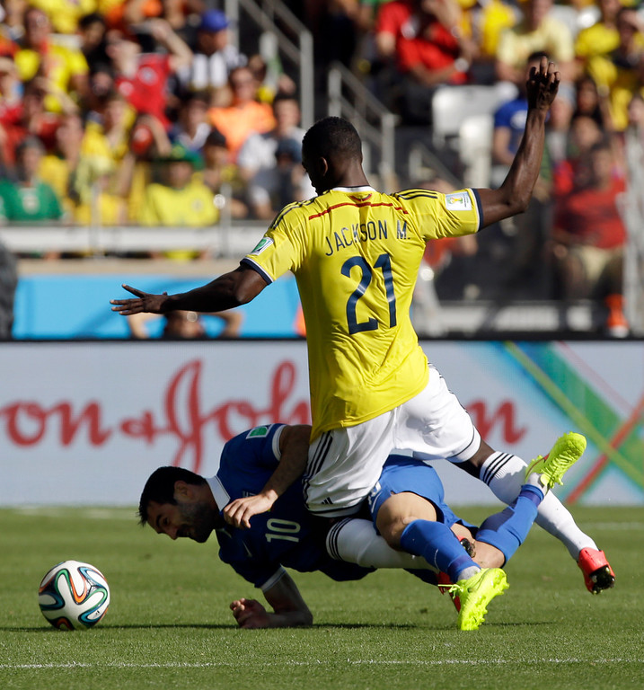 . Colombia\'s Jackson Martinez (21) is tangled up with Greece\'s Giorgos Karagounis during the group C World Cup soccer match between Colombia and Greece at the Mineirao Stadium in Belo Horizonte, Brazil, Saturday, June 14, 2014. Greece won 3-0. (AP Photo/Fernando Vergara)