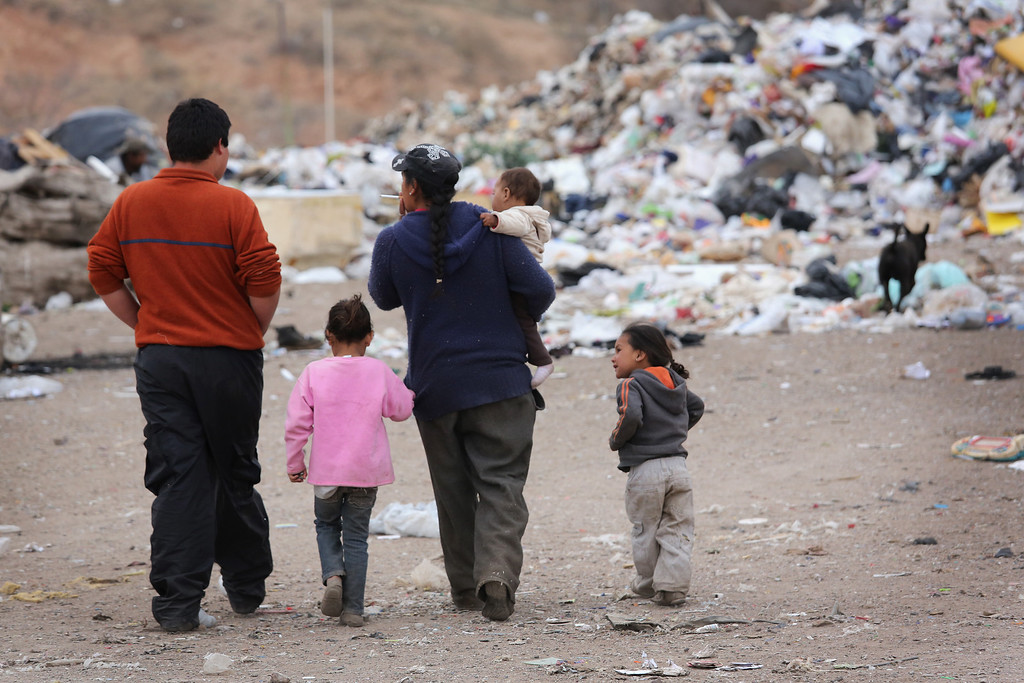 . NOGALES, MEXICO - MARCH 05:  A family walks through the Tirabichi garbage dump on March 5, 2013 in Nogales, Mexico. About 30 families live at the landfill, searching for recyclables to sell for a living. Some residents there were undomumented immigrants who were caught and deported by the United States back to Mexico. While living at the dump, they have received aid from the non-profit Home of Hope and Peace, which plans to expand its assistance to the dump\'s impoverished populace in the future.  (Photo by John Moore/Getty Images)