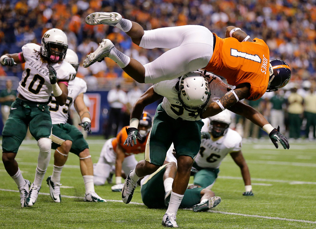 . UTSA\'s Kam Jones (1) is upended by UAB defender D.J. White as he scores a touchdown during the first half of an NCAA college football game, Saturday, Oct. 26, 2013, in San Antonio. (AP Photo/Eric Gay)