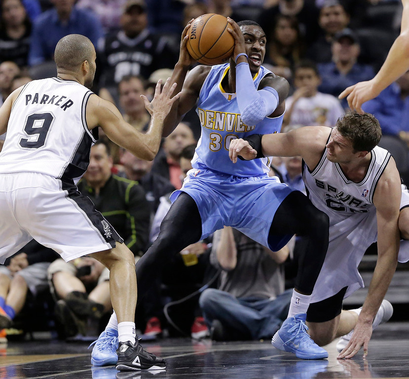 . Denver Nuggets\' Quincy Miller, center, grabs a loose ball as San Antonio Spurs\' Tony Parker (9) and Tiago Splitter, right, close in during the first half of an NBA basketball game, Wednesday, March 26, 2014, in San Antonio. (AP Photo/Eric Gay)