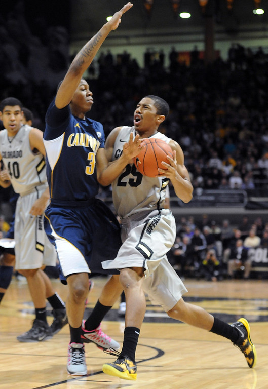 . Spencer Dinwiddie of CU drives into Tyrone Wallace of Cal during the first half of the January 27th, 2013 game in Boulder. Cliff Grassmick/The Daily Camera