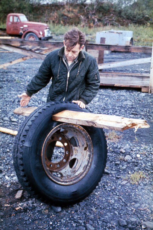 . Alaska Earthquake March 27, 1964. Indication of the violence of the surge waves that struck Whittier: man holds mounted ten-ply tire through which a 2 by 6-inch plank of wood has been driven by a wave. U.S. Geological Survey photo