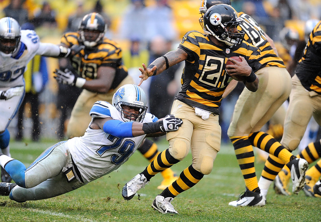 . Le\'Veon Bell #26 of the Pittsburgh Steelers avoids a tackle by Willie Young #79 of the Detroit Lions during the second quarter on November 17, 2013 at Heinz Field in Pittsburgh, Pennsylvania.  (Photo by Joe Sargent/Getty Images)