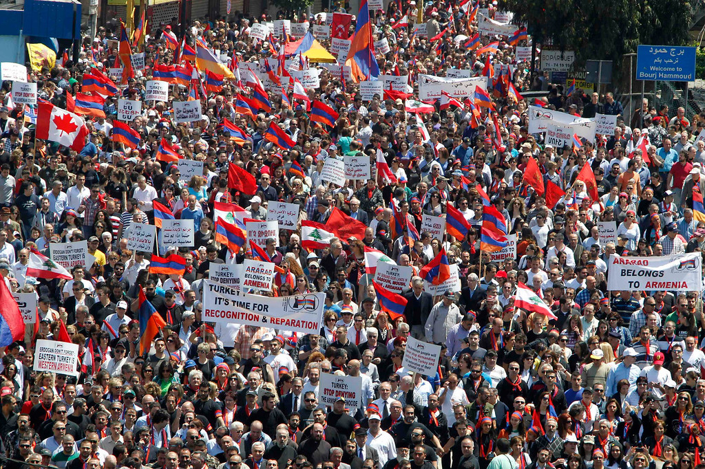 . Lebanese of Armenian descent carry banners as they wave Lebanese and Armenian flags during a march from Bourj Hammoud to downtown Beirut\'s Martyrs Square, April 24, 2013, to mark the 98th anniversary of the mass killing of Armenians in the Ottoman Empire in 1915. REUTERS/Sharif Karim