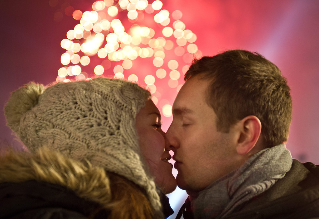 . A couple kiss as fireworks illuminate the night sky over the Brandenburger Tor to welcome in the new year in Berlin, Germany, 01 January 2014.  EPA/OLE SPATA