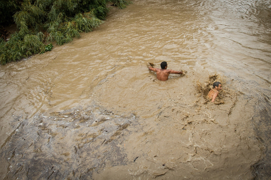 . Two young men turn back down from swimming under the flooded bridge on Broadway over Boulder Creek after bystanders shouted at them to stop.¬�