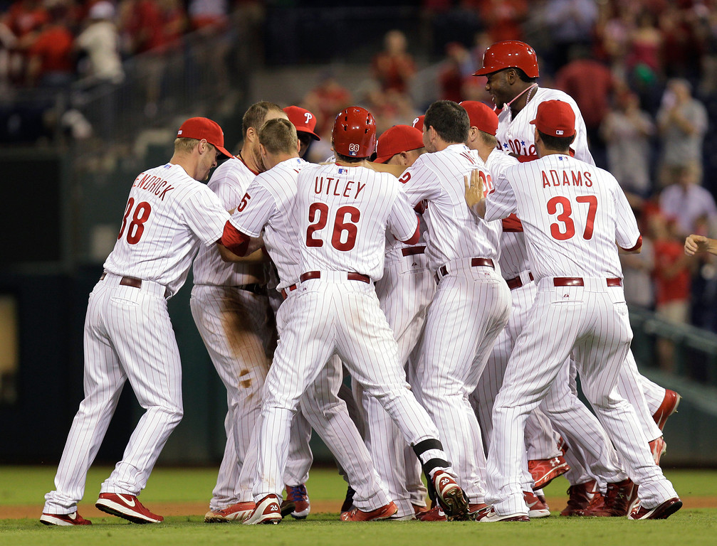 . The Philadelphia Phillies celebrate Michael Young\'s game-winning hit in the ninth inning against the Colorado Rockies in a baseball game, Wednesday, Aug. 21, 2013, in Philadelphia. The Phillies won 4-3. (AP Photo/Laurence Kesterson)