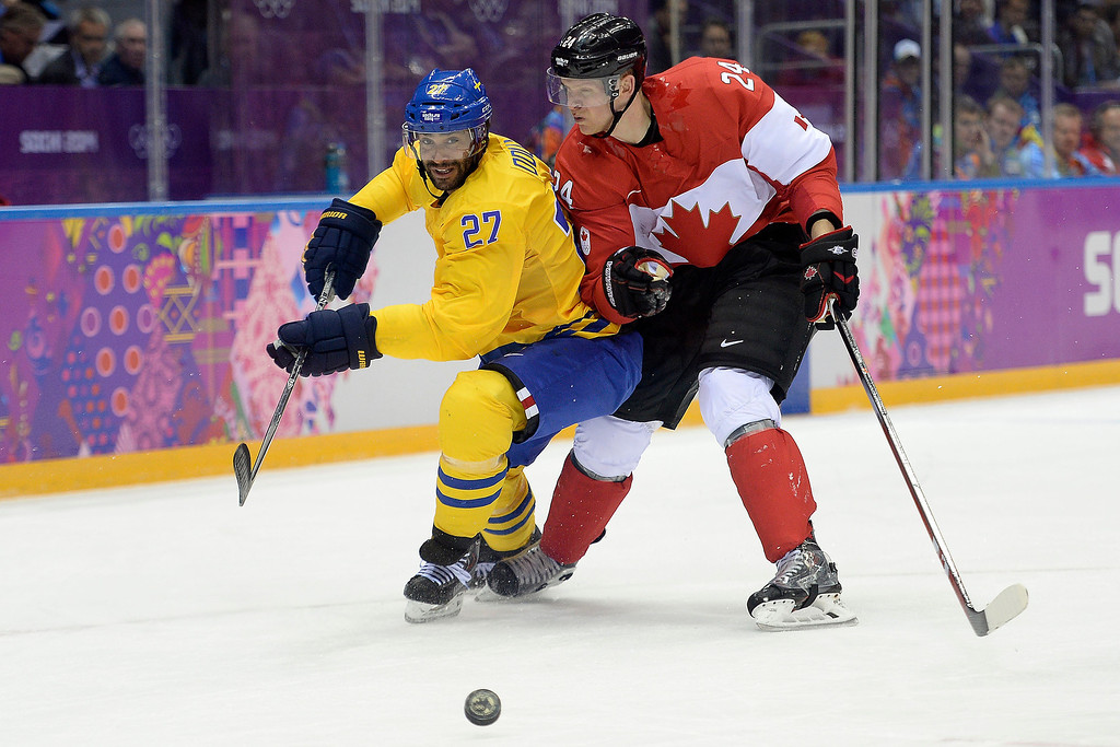 . Johnny Oduya (27) of Sweden and Corey Perry (24) of Canada jockey for position during the first period of the men\'s ice hockey gold medal game. Sochi 2014 Winter Olympics on Sunday, February 23, 2014 at Bolshoy Ice Arena. (Photo by AAron Ontiveroz/ The Denver Post)