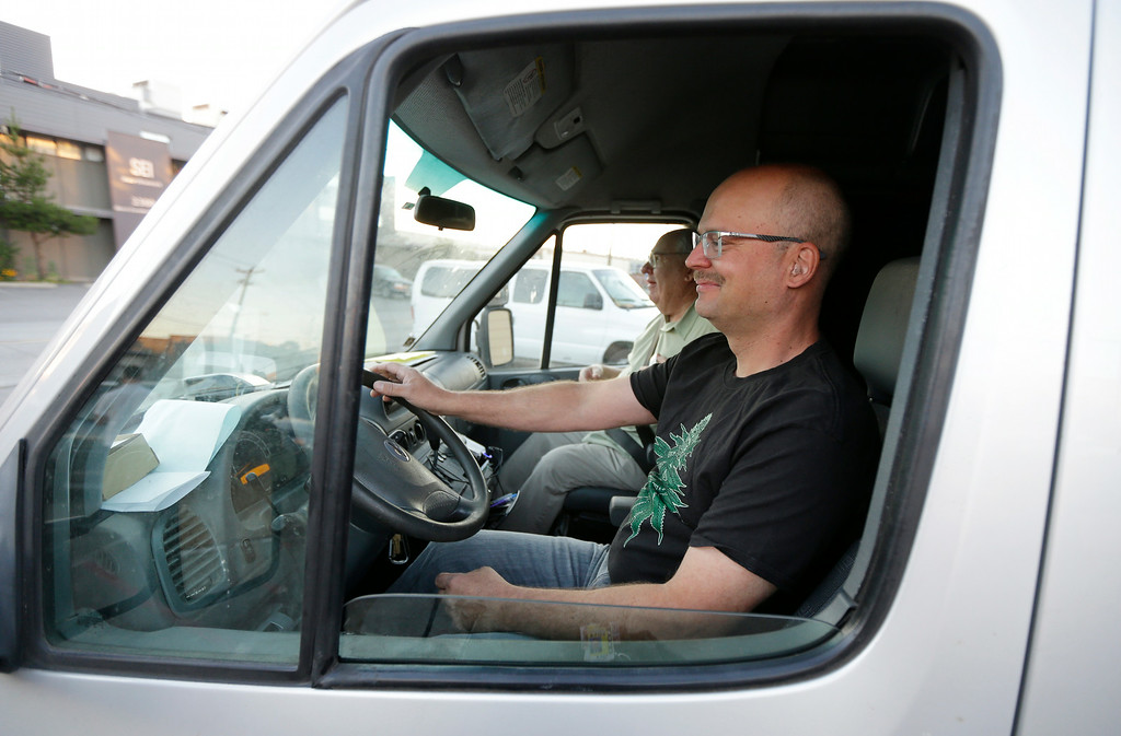 . Phil Tobias, director of Sea of Green Farms, front, drives a delivery van in Seattle with farm owner Bob Leeds, as they set out on their first delivery of recreational marijuana to a store in Bellingham, Wash., on Tuesday, July 8, 2014. It was the first delivery for the company since retail licenses were issued by the state on Monday. (AP Photo/Ted S. Warren)