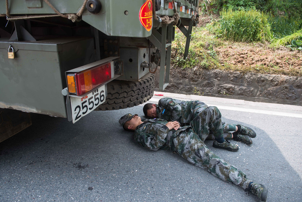 . This photo taken on April 21, 2013 shows rescuers sleeping on the road in the disaster-hit area in Ya\'an, southwest China\'s Sichuan province. STR/AFP/Getty Images