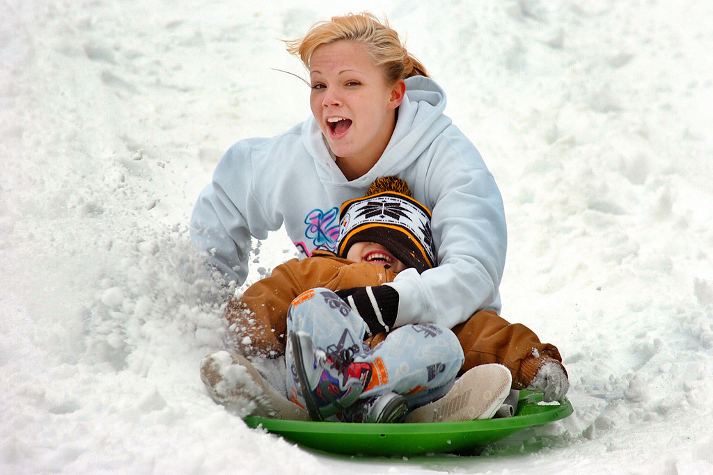 . After a push from Niles Durazno,   Shelby McVey and their son, Kaden Durazno, 3, blast through the snow Wednesday, March 6, 2013, on a hill at Matter Park in Marion, Ind. Grant County received between 5 and 7 inches of snow overnight.  (AP Photo/The Chronicle-Tribune,Jeff Morehead )