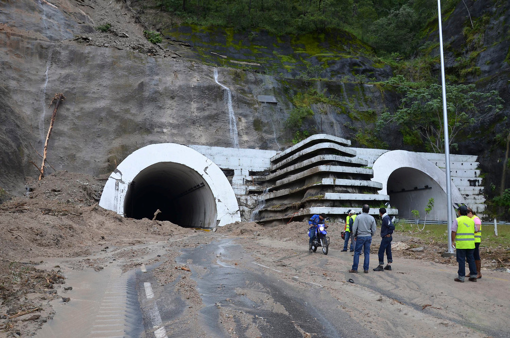 . People stand at the entrance to the badly damaged Agua de Obispo tunnel that connects Acapulco and Chilpancingo, near Chilpancingo, Mexico, Tuesday, Sept. 17, 2013. As many as 60,000 tourists, many of whom traveled from Mexico City for a long holiday weekend, found themselves stranded in Acapulco, with the airport flooded and highways blocked by landslides and water caused by Tropical Storm Manuel. (AP Photo/Alejandrino Gonzalez)