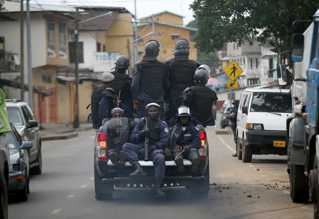 . MONROVIA, LIBERIA - AUGUST 20:  Members of Liberia\'s Ebola Task Force ride in the back of a pickup as they enforce a quarantine on the West Point slum on August 20, 2014 in Monrovia, Liberia. The military began enforcing a quarantine on West Point, a congested favela of 75,000, fearing a spread of the Ebola epidemic in the capital city. Liberian soldiers were also sent in to extract West Point Commissioner Miata Flowers and her family members after residents blamed the government for setting up a holding center for suspected Ebola patients in their community. A mob overran and closed the facility on August 16. The Ebola virus has killed more than 1,200 people in four African nations, more in Liberia than any other country.  (Photo by John Moore/Getty Images)