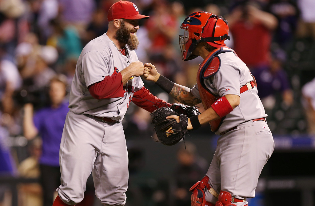 . St. Louis Cardinals relief pitcher Jason Motte, left, is congratulated by catcher Yadier Molina after retiring Colorado Rockies\' Troy Tulowitzki for the final out in the ninth inning of the Cardinals\' 8-0 victory in a baseball game in Denver on Monday, June 23, 2014. (AP Photo/David Zalubowski)