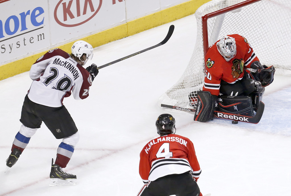 . Chicago Blackhawks goalie Corey Crawford (50) makes a save on a shot by Colorado Avalanche center Nathan MacKinnon (29) as Niklas Hjalmarsson (4) watches during the second period of an NHL hockey game Tuesday, March 4, 2014, in Chicago. (AP Photo/Charles Rex Arbogast)