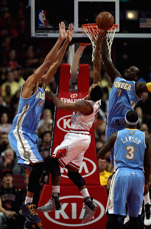 . J.J. Hickson #7 of the Denver Nuggets blocks a shot by Derrick Rose #1 of the Chicago Bulls as JaVale McGee #34 defends during a preseason game at the United Center on October 25, 2013 in Chicago, Illinois. (Photo by Jonathan Daniel/Getty Images)