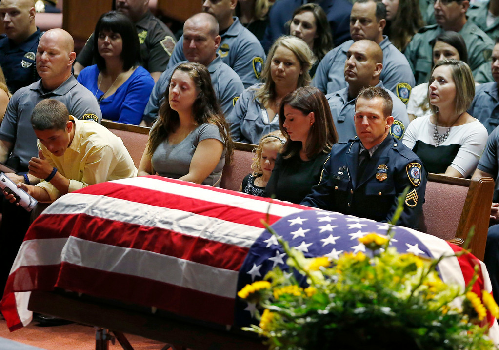 . Oklahoma City police officer Sgt. Ryan Stark, right, looks at the casket of his canine partner, K-9 Kye, during funeral services for the dog at First Southern Baptist Church in Oklahoma City, Thursday, Aug. 28, 2014. (AP Photo/Sue Ogrocki)