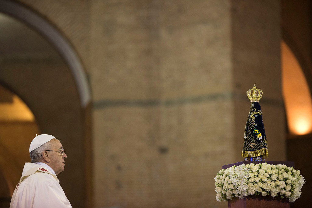 ". Pope Francis faces the statue of the Virgin of Aparecida, Brazil\'s patron saint, in the Aparecida Basilica, in Aparecida, Brazil, Wednesday, July 24, 2013. Before the Mass, Francis stood in silent prayer in front of the 15-inch statue of the Virgin of Aparecida, the ""Black Mary,\"" his eyes tearing up. (AP Photo/Felipe Dana)"