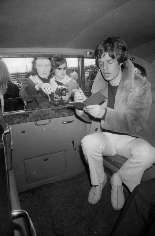 . Mick Jagger, the lead singer of the Rolling Stones, signing autographs for fans at London Airport, April 6, 1966.  (Photo by Express/Express/Getty Images)