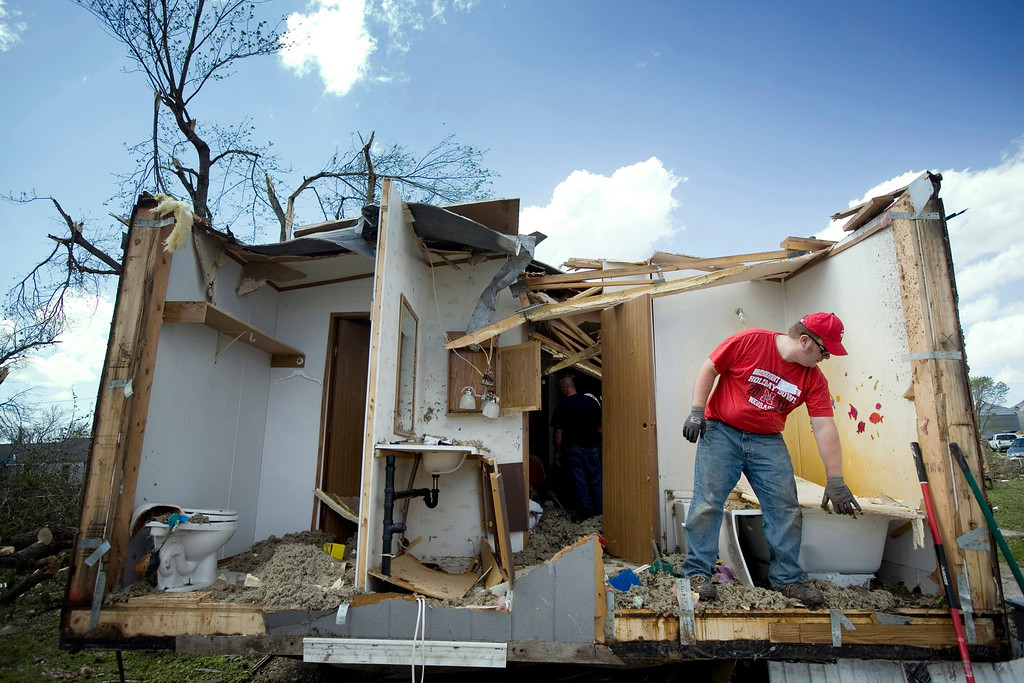 . Tim Crom picks up debris from a damaged home in Thurman, Iowa April 15, 2012. Rescue and clean-up efforts were underway across the Midwest on Sunday after dozens of tornados tore through the region, killing at least five people in Oklahoma, leaving thousands without power in Kansas and damaging up to 90 percent of the homes and buildings in one small Iowa town.   REUTERS/Lane Hickenbottom