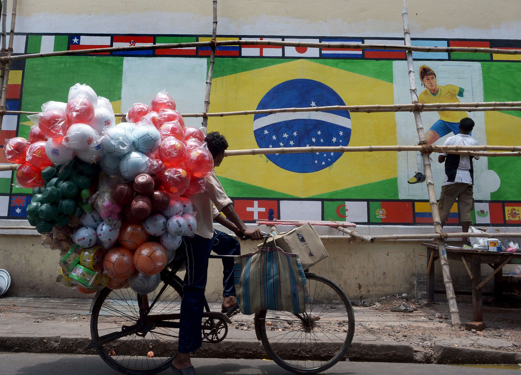 . An Indian artist gives finishing touches graffiti of Brazilian soccer player Neymar as a plastic football vendor looks on at the roadside in Kolkata on June 10, 2014. Football fans in the eastern Indian city are gearing up for the upcoming Brazil FIFA World Cup 2014 and decorating their clubs with football-related paraphernalia. AFP PHOTO/ Dibyangshu SARKAR/AFP/Getty Images