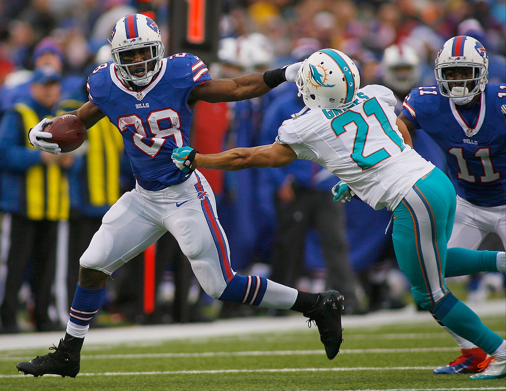 . C.J. Spiller #28 of the Buffalo Bills runs against   Brent Grimes #21 of the Miami Dolphins at Ralph Wilson Stadium on December 22, 2013 in Orchard Park, New York. Buffalo won 16-0.  (Photo by Rick Stewart/Getty Images)