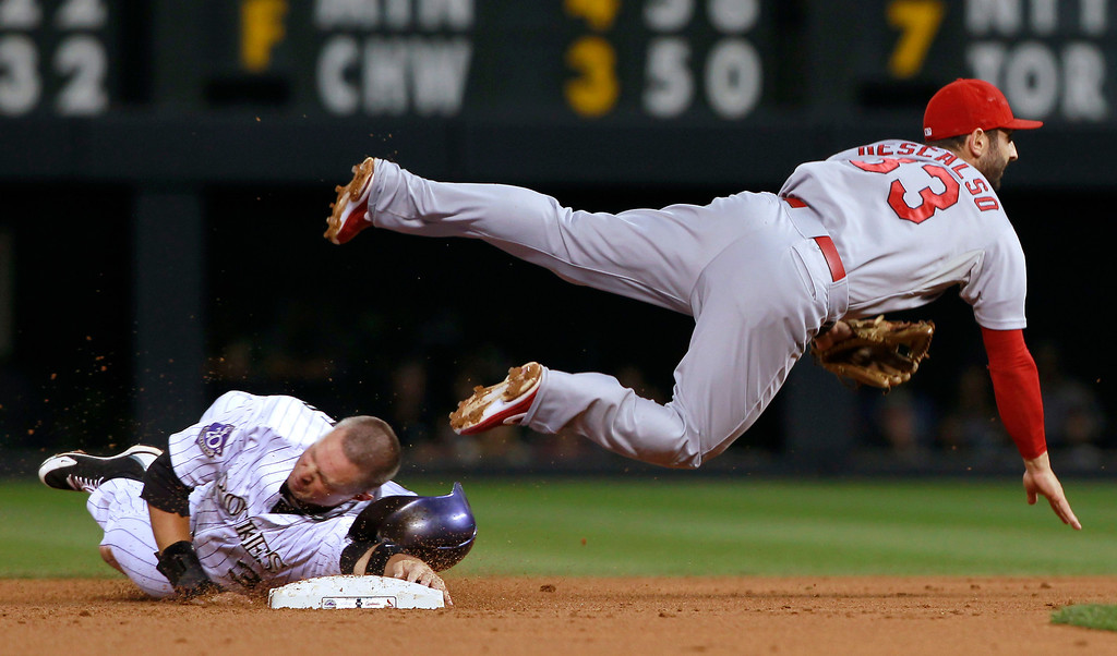 . St. Louis Cardinals shortstop Daniel Descalso, right, watches his throw to first after forcing out Colorado Rockies\' Michael Cuddyer at secondon the front end of a double play hit into by Todd Helton in the first inning of a baseball game in Denver on Wednesday, Sept. 18, 2013. (AP Photo/David Zalubowski)