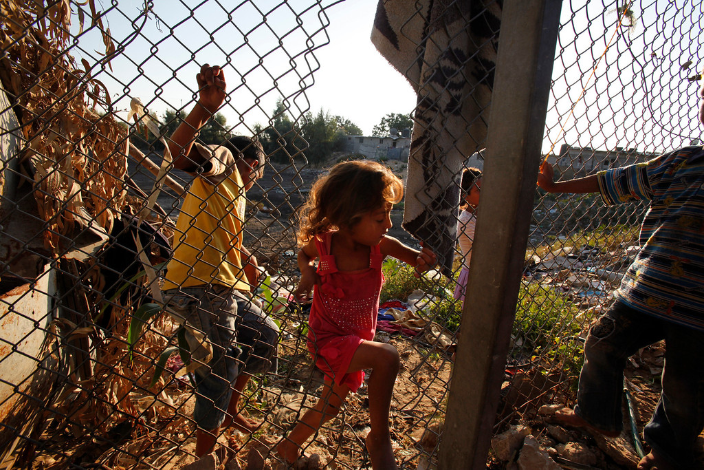 . In this Tuesday, Oct. 1, 2013 photo, Heba Alwadiya, 6, passes through a hole made in a fence to gain access to her family house in Gaza City. Their family\'s only form of transportation is a donkey cart. (AP Photo/Adel Hana)