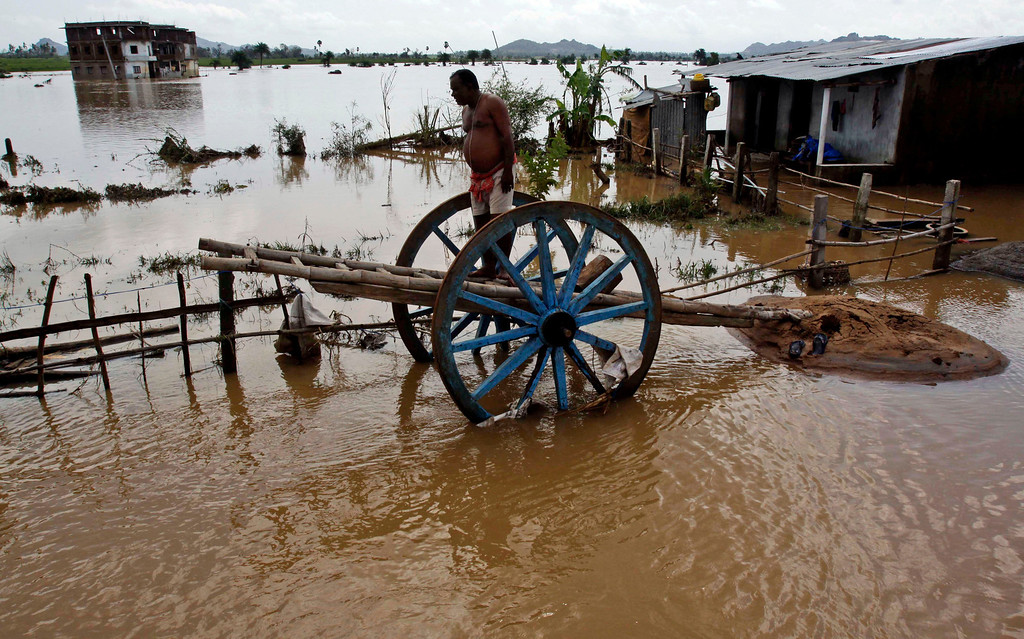 . An Indian villager stands on a cart outside his home surrounded by floodwaters at Purushatampur in Ganjam district of Orissa state, India, Saturday, Oct. 26, 2013. Days of torrential rains have unleashed floods in the states of Andhra Pradesh and Orissa, killing dozens of people and forced the evacuation of more than 70,000 others from hundreds of low-lying villages. As of Saturday, 39 people had died in flood-related incidents in the two states since the rains began Monday, according to officials quoted by the Press Trust of India. (AP Photo/Biswaranjan Rout)