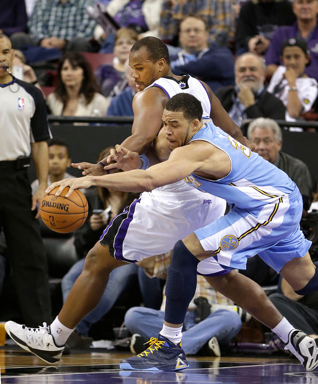 . Denver Nuggets center JaVale McGee, right, scrambles after a loose ball against     Sacramento Kings forward Chuck Hayes, during the fourth quarter of an NBA basketball game in Sacramento, Calif., Tuesday, March 5, 2013.  The Nuggets won 120-113.(AP Photo/Rich Pedroncelli)