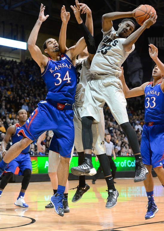 . Colorado University guard, Jaron Hopkins, right, grabs a rebound against Kansas forward, Perry Ellis, left, in the first half of play at the Coors Events Center in Boulder Colorado Saturday afternoon, December 07, 2013. (Photo By Andy Cross/The Denver Post)