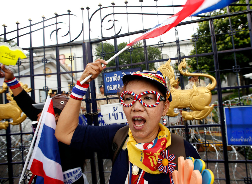 . A Thai anti-government protester waves a national flag as security personnel guards behind the gate during a massive rally occupying the Interior Ministry in Bangkok, Thailand, 26 November 2013.  EPA/RUNGROJ YONGRIT