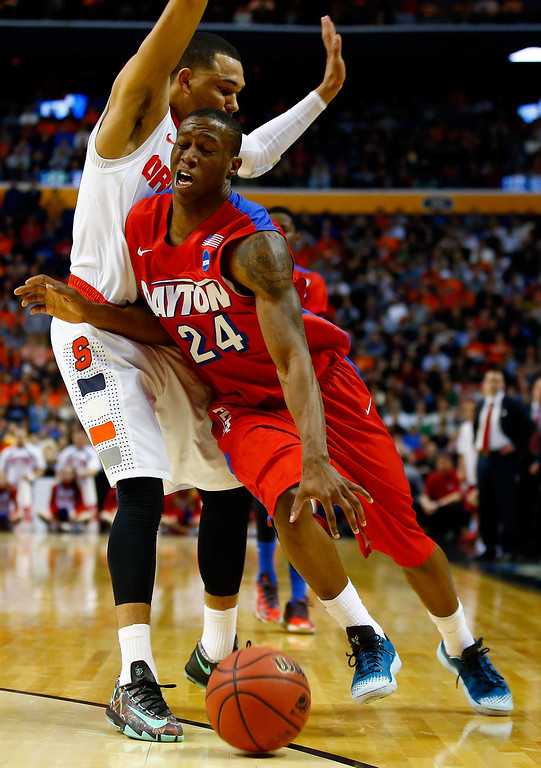 . BUFFALO, NY - MARCH 22: Jordan Sibert #24 of the Dayton Flyers drives to the basket as Tyler Ennis #11 of the Syracuse Orange defends during the third round of the 2014 NCAA Men\'s Basketball Tournament at the First Niagara Center on March 22, 2014 in Buffalo, New York.  (Photo by Jared Wickerham/Getty Images)