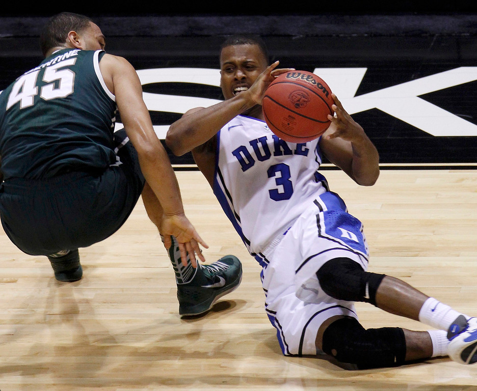. Duke Blue Devils guard Tyler Thornton (3) goes down on the court with Michigan State Spartans guard Denzel Valentine (45) in the first half during their Midwest Regional NCAA men\'s basketball game in Indianapolis, Indiana, March 29, 2013. REUTERS/Matt Sullivan