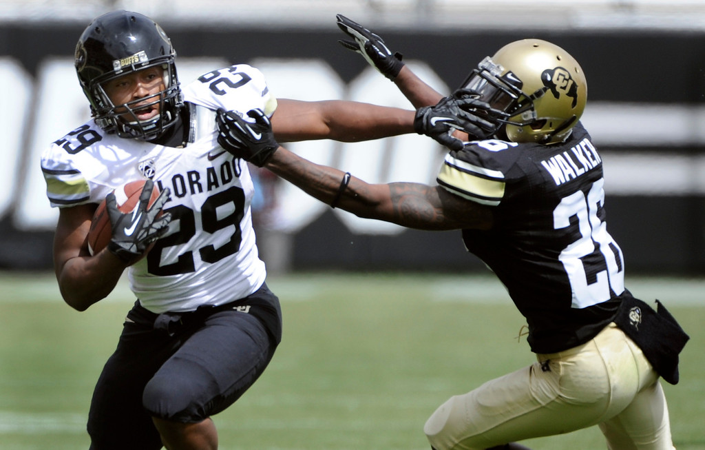 . BOULDER, CO.- APRIL13: Josh Ford, left, pushes away defensive back John Walker. The University of Colorado football team hosts its spring football game at Folsom Field under the direction of new head coach Mike MacIntyre. (Photo By Kathryn Scott Osler/The Denver Post)