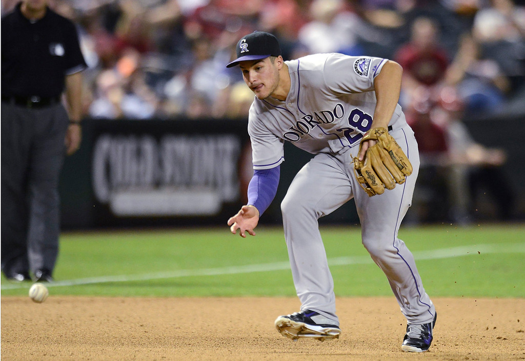 . Nolan Arenado #28 of the Colorado Rockies bare hands a ground ball against the Arizona Diamondbacks in the seventh inning at Chase Field on April 28, 2014 in Phoenix, Arizona.  (Photo by Norm Hall/Getty Images)