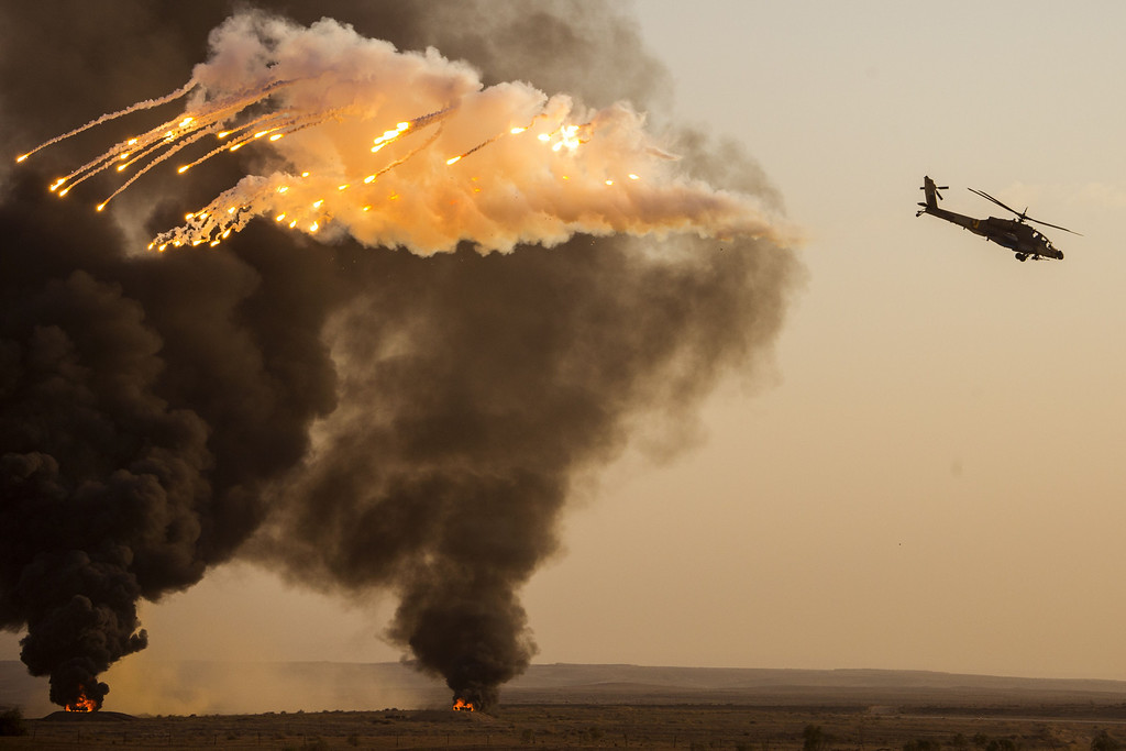 . An Israeli AH-64 Apache longbow helicopter launches anti-missile flares during an air show at the graduation ceremony of Israeli air force pilots at the Hatzerim base in the Negev desert, near the southern Israeli city of Beersheva on December 26, 2013. AFP PHOTO / JACK  GUEZ/AFP/Getty Images
