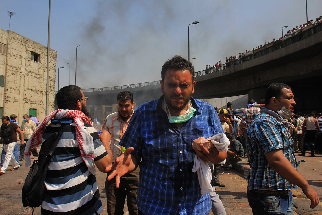 . Supporters of Egypt\'s ousted President Mohammed Morsi react to tear gas during clashes with security forces near the largest sit-in by supporters of Morsi in the eastern Nasr City district of Cairo, Egypt, Wednesday, Aug. 14, 2013.  (AP Photo/Mohammed Abu Zeid)