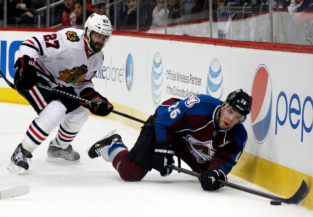 . Colorado Avalanche center Paul Stastny, right, reaches out for a loose puck as Chicago Blackhawks defenseman Johnny Oduya covers in the first period of an NHL hockey game in Denver, Friday, March 8, 2013. (AP Photo/David Zalubowski)