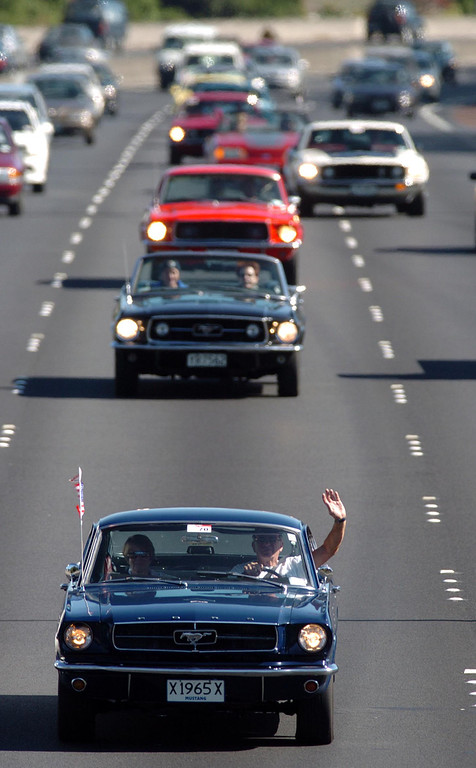. Denis Jones (R) and Vickie Steel (L) both from Takapuna, wave from their Ford Mustang as they lead a group of Mustangs on Auckland\'s Southern Motorway, New Zealand, Tuesday, March 30th, 2004 during the 2004 Kaitaia to Bluff Mustang Run. The event lasted 12 days, and consisted of about 40 NZ cars is to celebrate 40 years of Mustangs after the first car rolled off the production line on the 9th of March 1964 in Ford America\'s Dearborn Production line.  (Photo by Phil Walter/Getty Images)