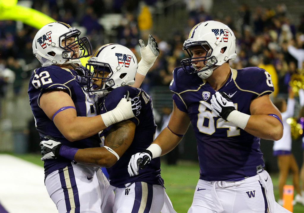 . Washington\'s Ross Dolbec (62) and Michael Hartvigson (84) celebrate after running back Dwayne Washington, center, scored a touchdown against Colorado in the second half of an NCAA college football game on Saturday, Nov. 9, 2013, in Seattle. Washington won 59-7. (AP Photo/Ted S. Warren)