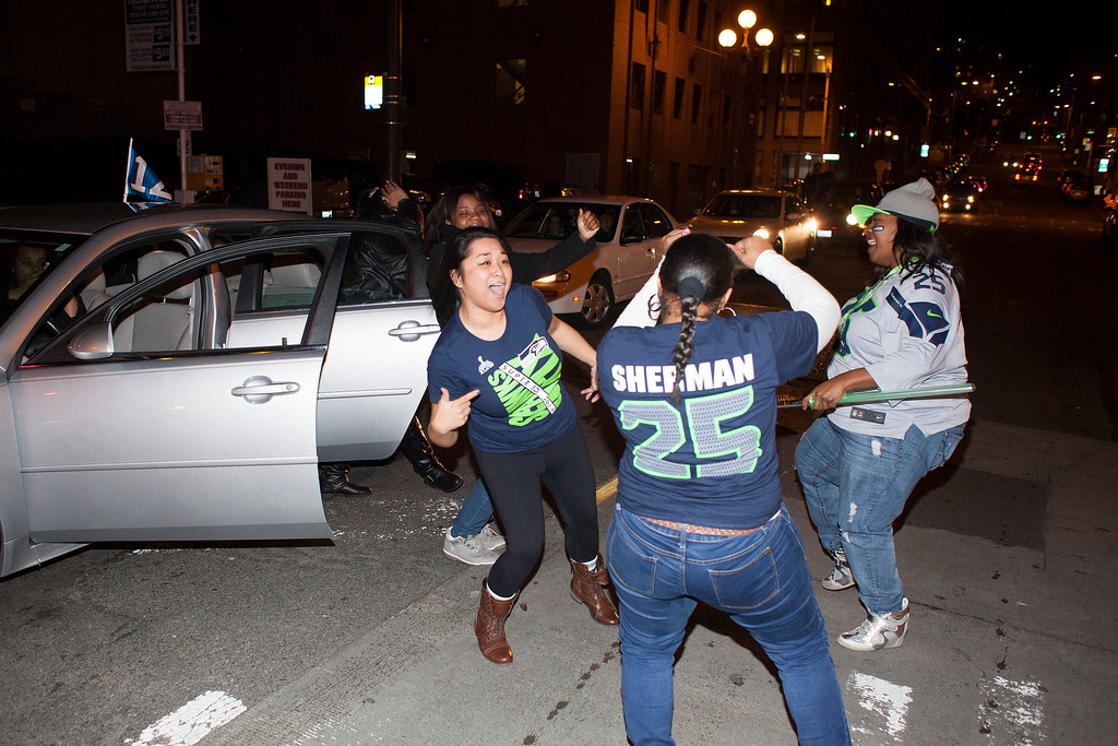 . Seattle Seahawks fans jump out of their car and dance in the middle of the street on February 2, 2014 in Seattle, Washington. Hundreds of people flooded the streets of downtown Seattle after the Seahawks defeated the Denver Broncos in the Super Bowl.  (Photo by David Ryder/Getty Images)