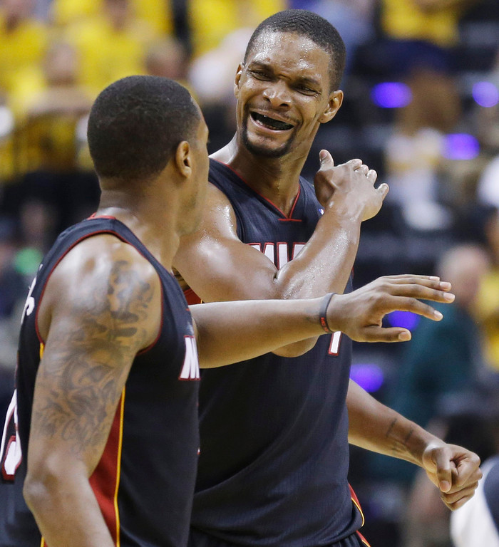 . Miami Heat guard Mario Chalmers, left, and center Chris Bosh celebrate during the second half against the Indiana Pacers in Game 5 of the NBA basketball Eastern Conference finals in Indianapolis, Wednesday, May 28, 2014. (AP Photo/Michael Conroy)