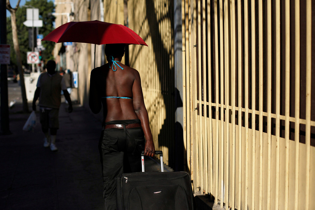 . A woman rolls her luggage down the sidewalk in the Skid Row area of Los Angeles, Tuesday, March 12, 2013. (AP Photo/Jae C. Hong)